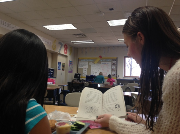 UW-Eau Claire senior Shalaine Buehl, right, reads Evie the Mist Fairy with Clarice Xiong, a third-grader at Lakeshore Elementary, on Friday, Dec. 4. Buehl travels to the elementary school every Friday afternoon to read with Xiong, who Buehl said expresses interest in any books related to fairies.